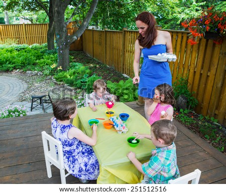 Family of children having fun painting and decorating Easter eggs outside.  Mother gives eggs to her children to color dye during the spring season in a beautiful garden setting.  Part of a series.   - stock photo