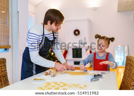 Family of father and daughter baking cookies at home on Xmas eve. Beautifully decorated room, fireplace,  Christmas tree and lights on background.