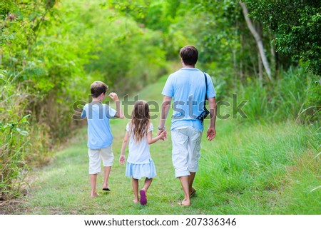 Family of father and kids hiking at forest or park at summer day - stock photo