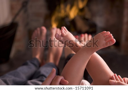 Family of feet warming at a fireplace - stock photo