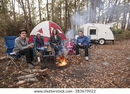 Family of five camping in the woods with campfire, tent, and teardrop trailer