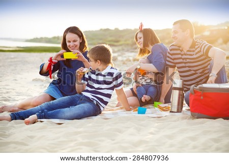 Family of five doing selfy at the picnic on the beach. Summer vacation concept - stock photo