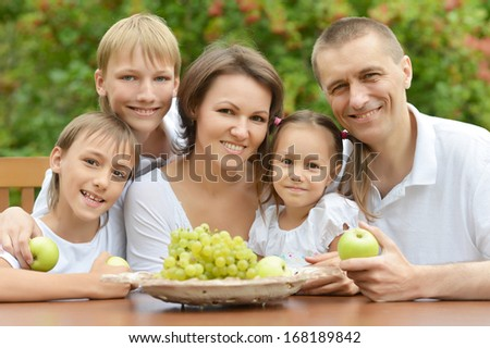 Family of five eating fruit at table outdoors in summer time