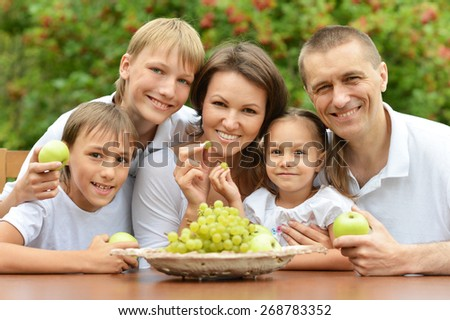 Family of five eating fruits at table outdoors in summer time - stock photo