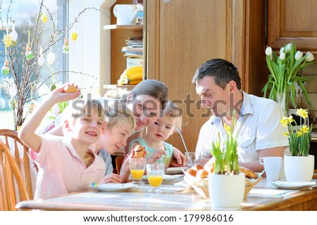 Family of five: father, mother and three kids, teenager sons and toddler daughter eating eggs during family breakfast on Easter day sitting together in sunny kitchen. Selective focus on little girl. - stock photo