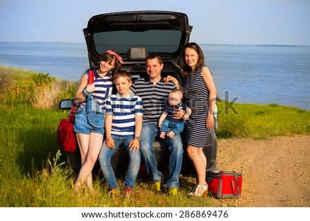 Family of five having fun on the beach going on summer vacation. Car travel and summer vacation concept