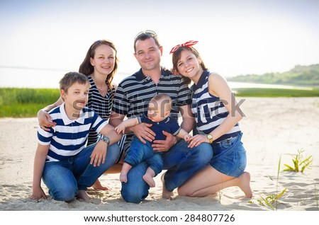 Family of five having fun on the beach. Summer vacation concept