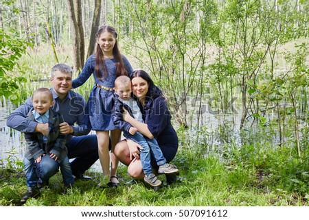 Family of five poses on boggy pond shore in summer park.
