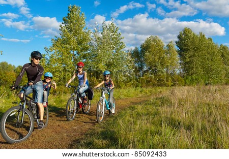 Family of four cycling outdoors. Happy parents with two kids on bikes - stock photo