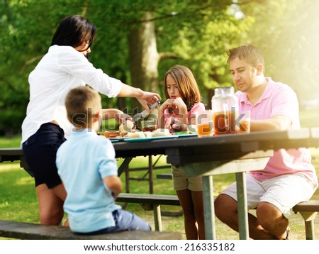family of four eating at barbecue cookout - stock photo
