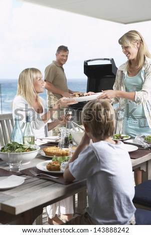 Family of four enjoying barbecue against the sea - stock photo