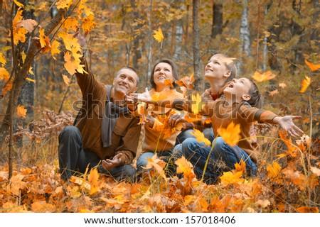 Family of four enjoying golden leaves in autumn park - stock photo