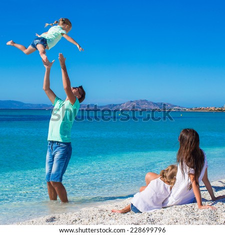 Family of four having fun during their tropical vacation - stock photo