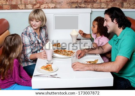 Family of four having great time in a restaurant - stock photo