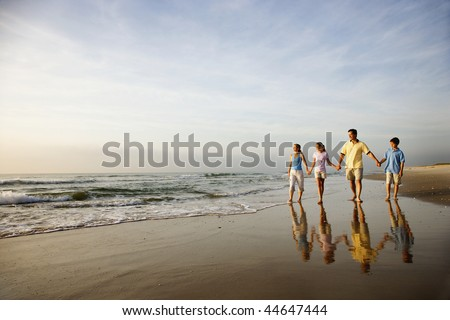 Family of four holding hands and walking on beach in North Carolina. - stock photo
