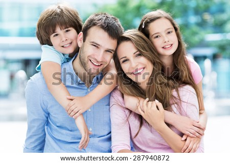 Family of four hugging each other  - stock photo
