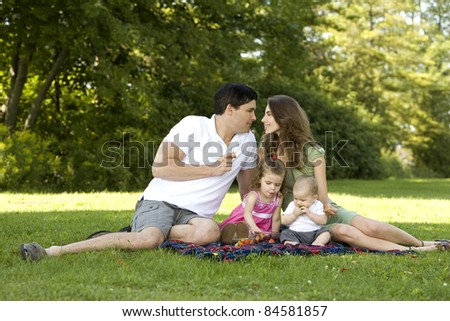 family of four in the park having fun together
