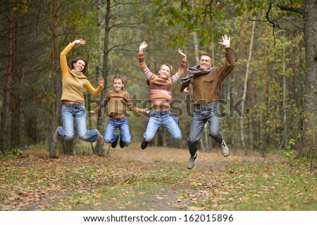 Family of four jumping in autumn forest - stock photo