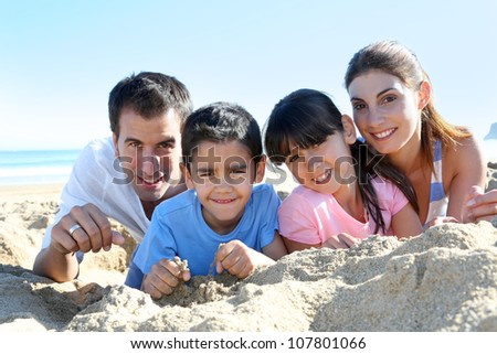 Family of four laying on a sandy beach - stock photo