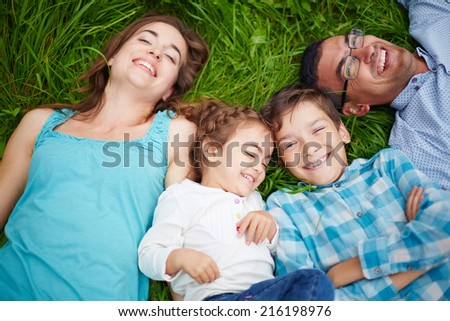 Family of four lying on green grass and looking at camera with smiles - stock photo