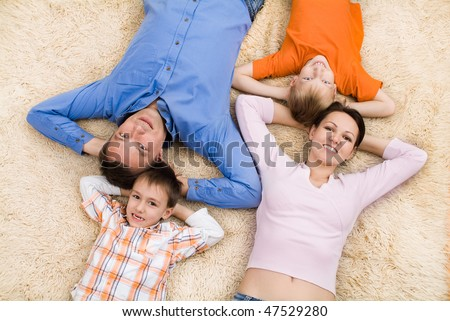 family of four lying on the carpet