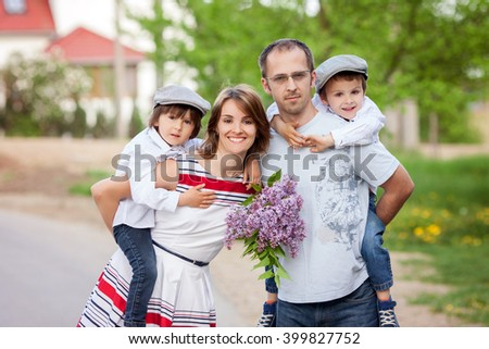 Family of four, mother, father and two boys, parent having the kids on piggy back, laughing, smiling, hugging, giving a kiss, holding flowers - stock photo