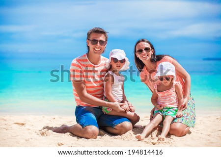 Family of four on happy beach vacation at tropical island - stock photo