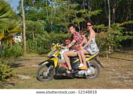 Family of four on motorbike. Family vacation - stock photo