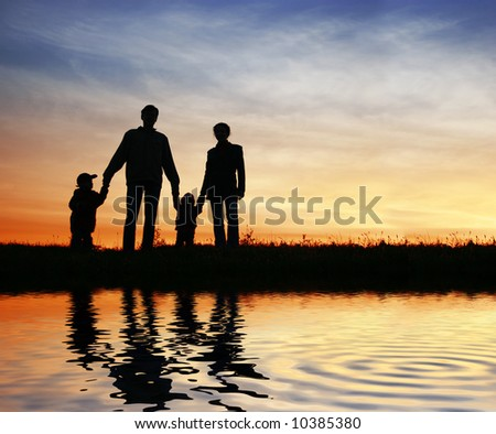 family of four on sunset sky, water - stock photo