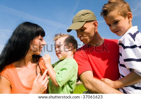 Family of four outdoors at a wonderful summer day - stock photo