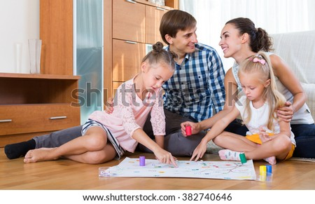 Family of four playing at board game in domestic interior - stock photo