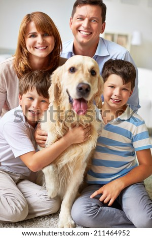 Family of four posing with their dog - stock photo