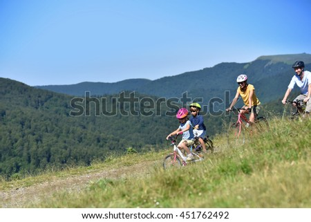 Family of four riding bikes in the mountain