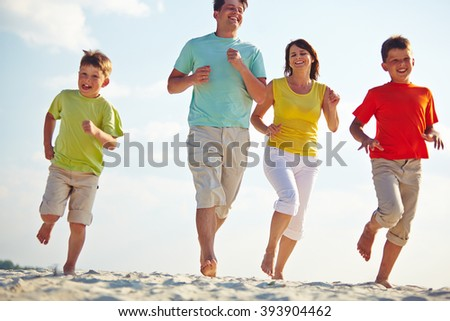 Family of four running on the beach - stock photo