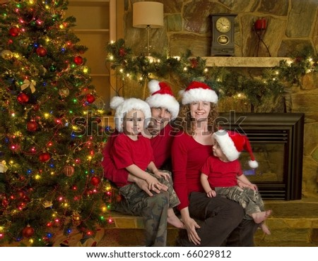 Family of Four sits beside Christmas Tree - stock photo