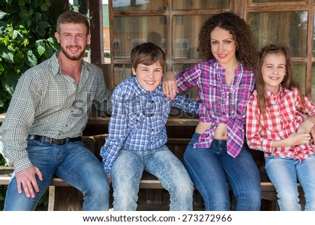 family of four sitting on a bench on background of wooden window - stock photo