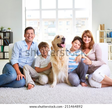 Family of four sitting on carpet - stock photo