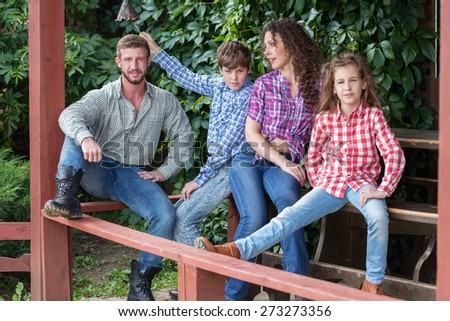 family of four sitting on terrace on background of green foliage - stock photo