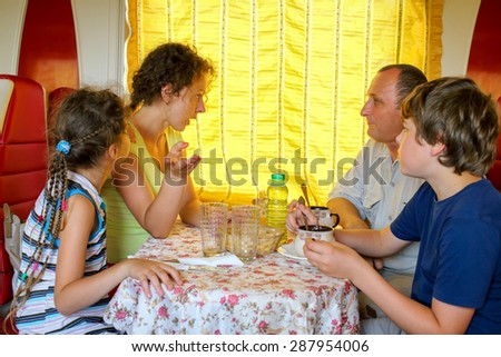 family of four talking  at a table in the dining car of the train - stock photo