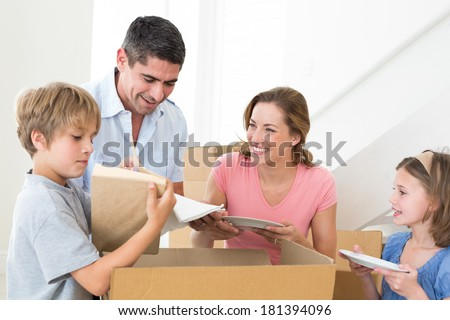 Family of four unpacking cardboard box in new house - stock photo