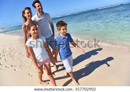 Family of four walking on a sandy caribbean beach  - stock photo