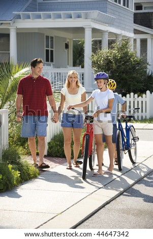 Family of four walking together on sidewalk with bicycles. - stock photo