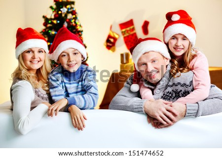 Family of four wearing Santa Claus caps being ready for Christmas - stock photo