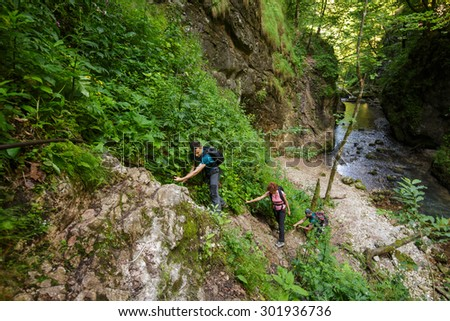 Family of hikers climbing on safety cables in a canyon - stock photo