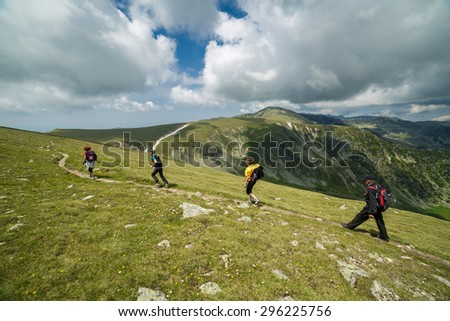 Family of hikers walking on a trail into the rocky mountains  - stock photo