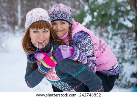 Family of mother and her adorable little daughter outdoors on beautiful winter day with snow. girls in winter forest  - stock photo
