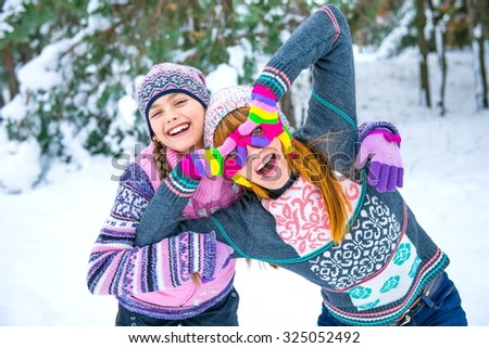 Family of mother and her adorable little daughter outdoors on beautiful winter day with snow. girls in winter forest. Two girls having fun in winter, winter fun outdoors - stock photo