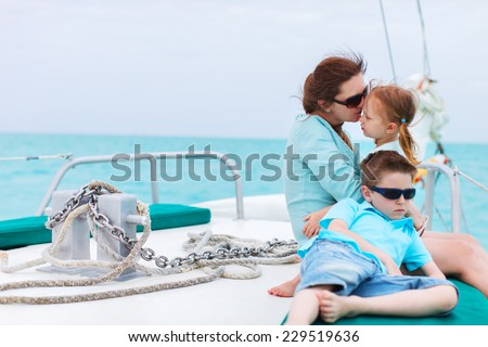 Family of mother and her kids having great time sailing at luxury yacht or catamaran boat - stock photo