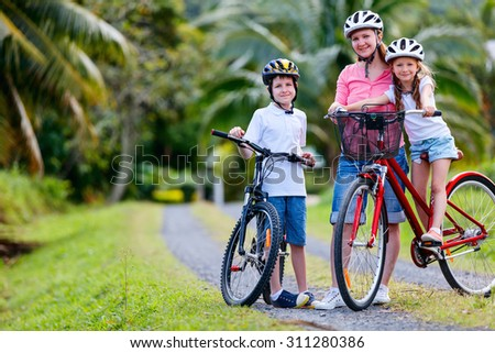 Family of mother and kids biking at tropical settings having fun together