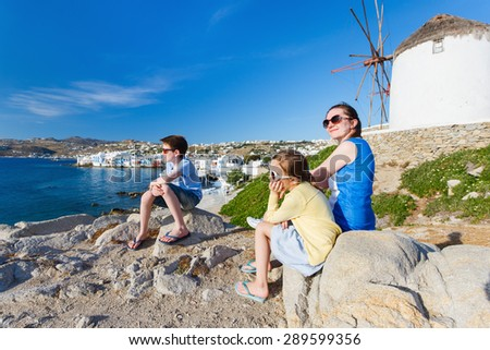 Family of mother and kids in front of windmills at popular tourist area on Mykonos island, Greece - stock photo